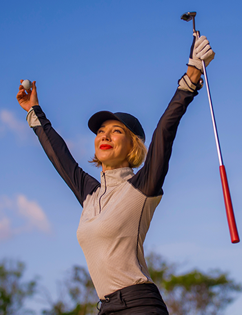 Woman golfer celebrating with her arms in the air